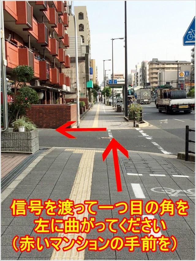 信号を渡って一つ目の角を左に曲がってください。赤いマンションの手前を